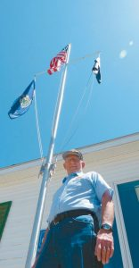 JOE DONAHUE of Brunswick's George T. Files Post 20 is pictured in front of the legion hall's new flag pole donated by a post member. Donahue has been selected as the Maine American Legion's legionnaire of the year.