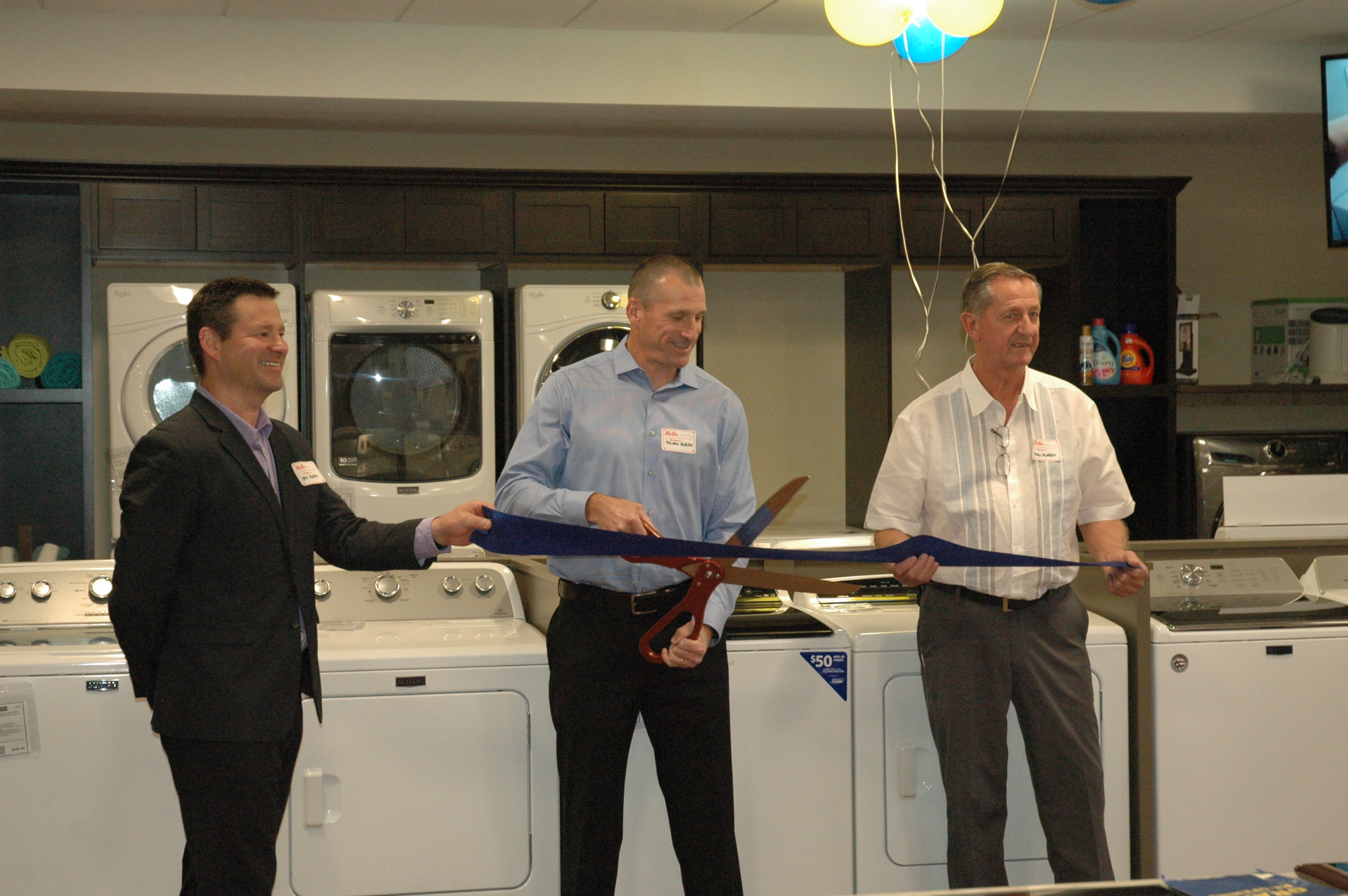 Jason Agren, center, prepares to cut a ribbon that his brother Eric, left, and father, Douglas, right, are holding at Agren Appliance in Saco on Friday.LIZ GOTTHELF/Journal Tribune