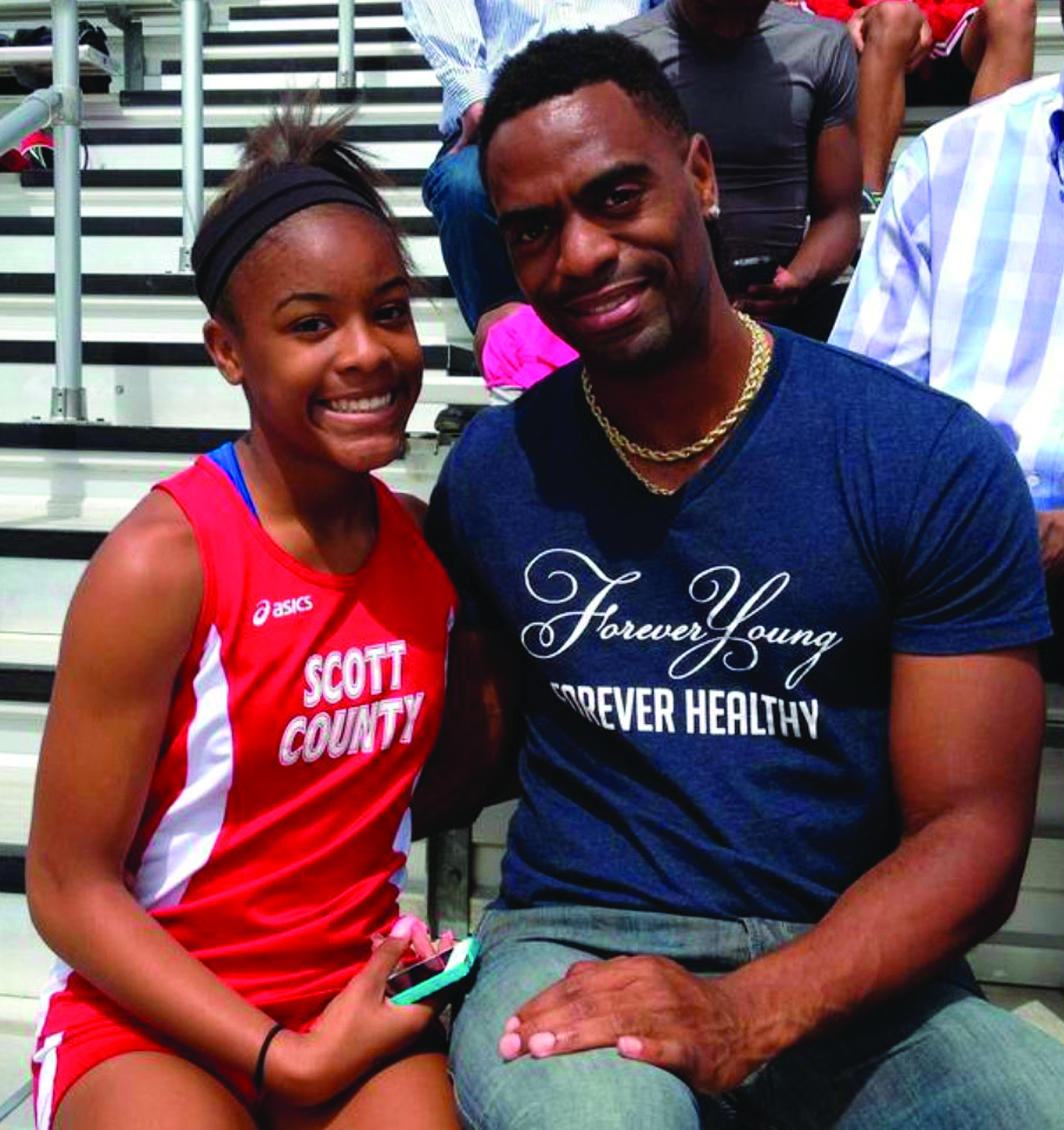 In this May 3, 2014, file photo, Trinity Gay, a seventh-grader racing for her Scott County High School team, poses for a photo with her father, Tyson Gay, after she won the 100 meters and was part of the winning 4-by-100 and 4-by-200 relays at the meet in Georgetown, Ky. The heartache still weighs heavily on Tyson Gay. But he keeps sprinting in her memory. The 15-year-old daughter of the Olympic sprinter was shot and killed in October outside a restaurant in Lexington, Kentucky. AP NEWSWIRE