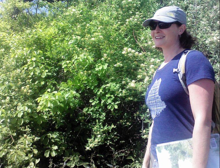 Kelly Corbin stands near honeysuckle at Fort Williams.