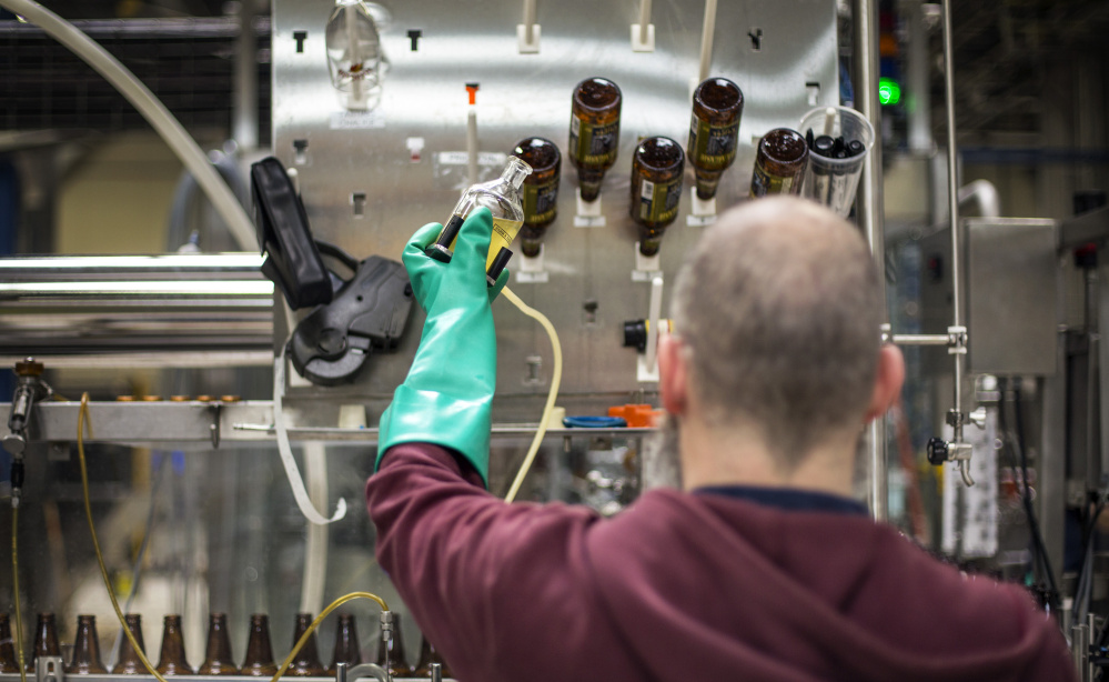 Rob Heater tests the carbonation of Tripel ale at Allagash Brewing Co. The quality of beer made by Allagash and others depends partly on wetlands and small streams that feed the systems from which their water is drawn.