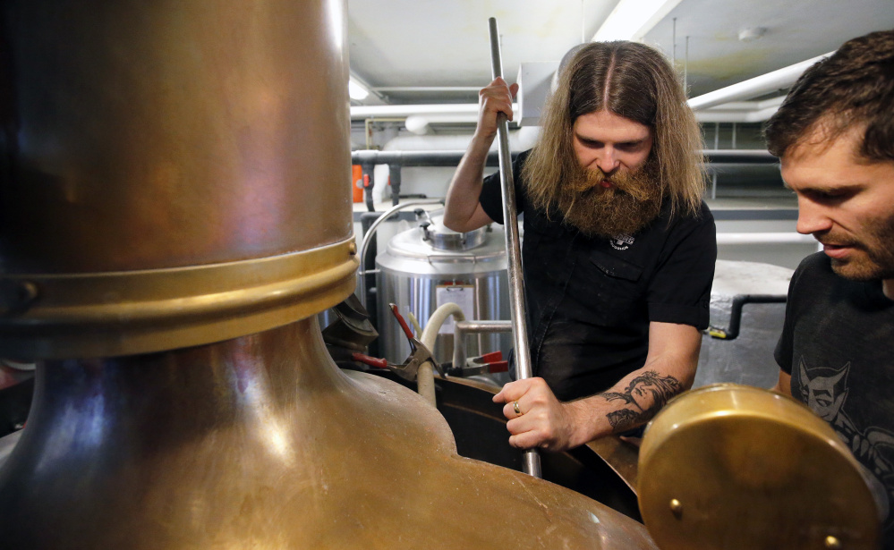 Sturlaugur Bjornsson, left, and Greg Abbot mix malt Thursday at Liquid Riot on Commercial Street for a small-batch beer. Bjornsson is brew master at Borg Brugghus – an unorthodox brewery in Iceland – while Abbot is head brewer at Liquid Riot.
