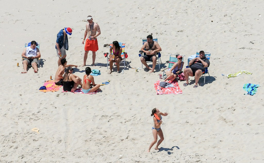 """New Jersey Gov. Chris Christie, right, uses the beach with his family and friends at the governor's summer house at Island Beach State Park in New Jersey on Sunday. Christie is defending his use of the beach, closed to the public during New Jersey's government shutdown, saying he had previously announced his vacation plans and the media had simply """"caught a politician keeping his word."""""""
