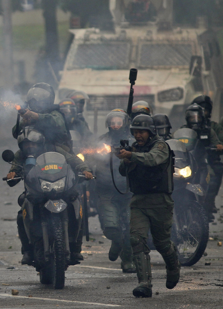 Venezuelan troops fire rubber bullets at anti-government protesters in Caracas last month.