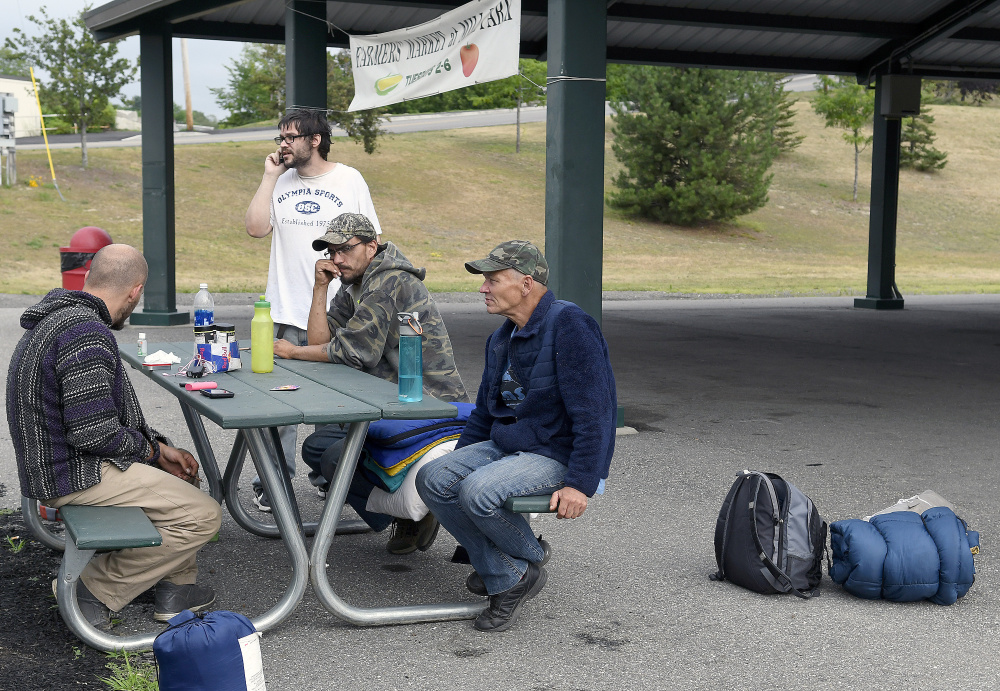 A group of homeless men discuss where to set up camp in Augusta. There's nothing prohibiting them from spending time on public property during the day, but camping out at night isn't allowed. Shelters are an option but fill up quickly. Staff photo by Andy Molloy