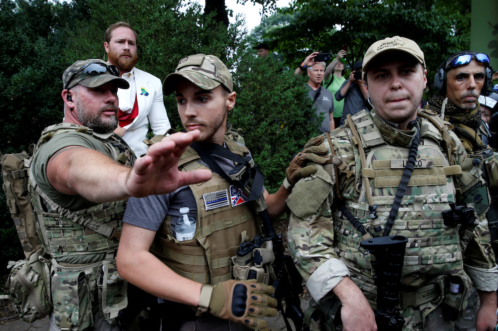 Heavily-armed white supremacist militia members surround a supporter after he scuffled with a counter demonstrator in Charlottesville, Virginia on August 12.