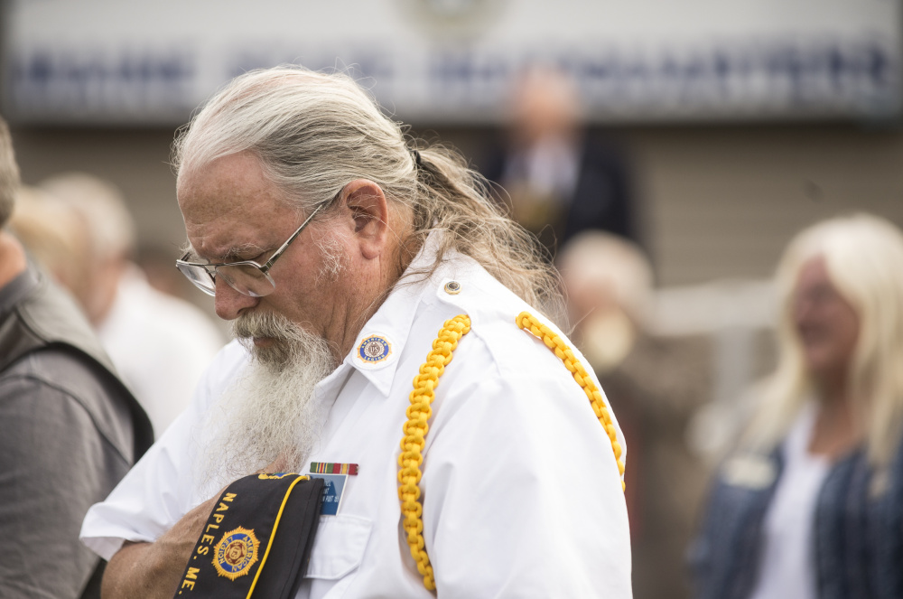 American Legion member Bill O'Neil lowers his head during a prayer Friday at the memorial groundbreaking at the Legion's Maine headquarters in Winslow.