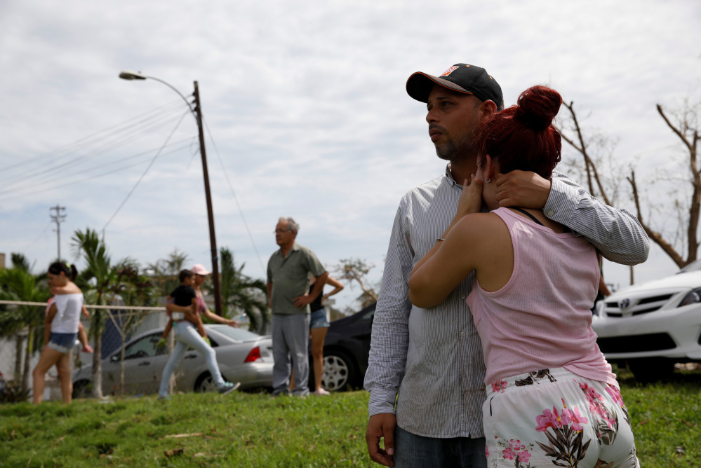 Local residents watch water flooding the road near the Lake  Guajataca dam. Thousands of people are awaiting evacuation.
