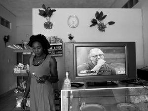 LUCY CHARLES, of Haiti, walks past a television in her restaurant specializing in Haitian cuisine in Tijuana, Mexico. The 33- year-old is among about 4,000 Haitians to establish roots in Mexico's northwest corner after the United States abruptly closed its doors late last year. The Mexican government has welcomed them, and they are already having an outsize economic and cultural impact.