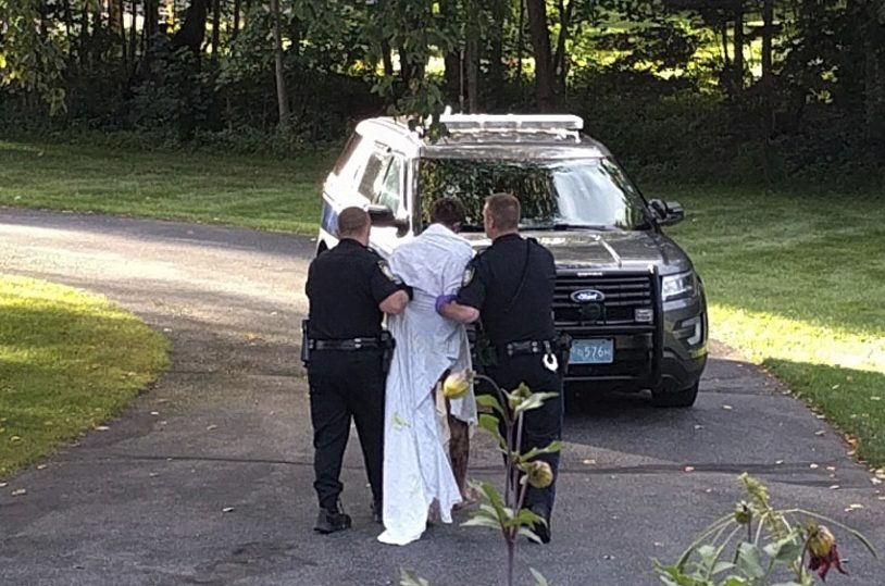 Police officers take Orion Krause, covered in a white sheet, to a police vehicle in Groton, Mass., on Sept. 8.