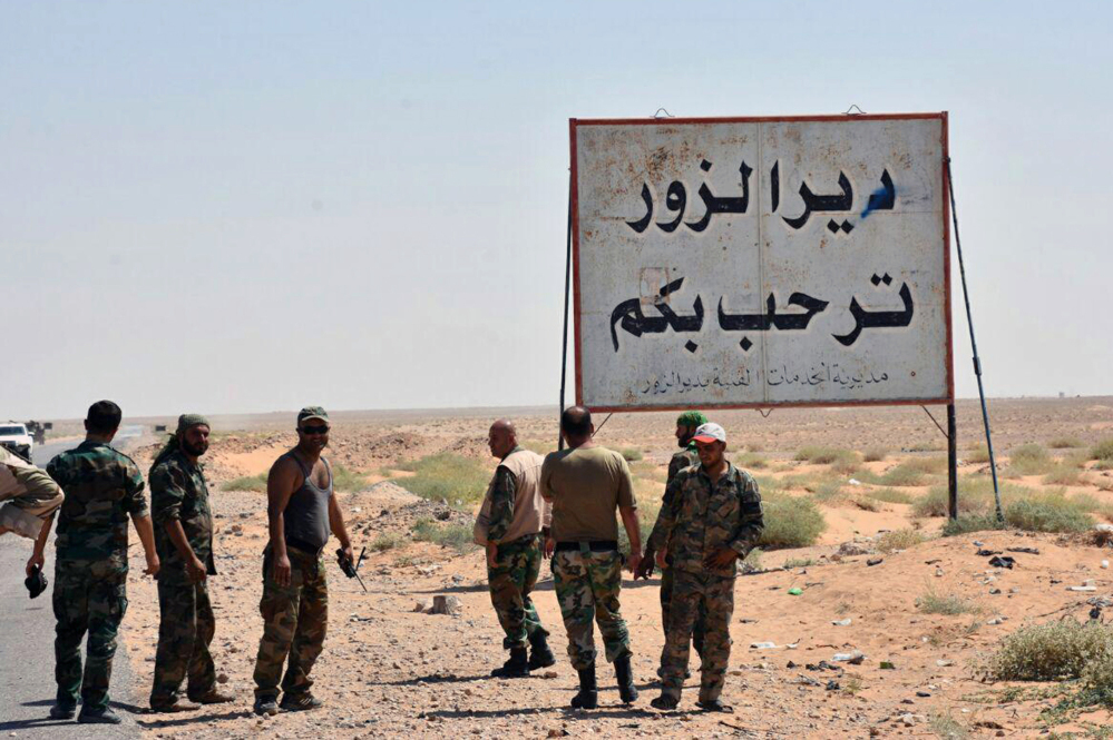 """A Sept. 3 photo shows Syrian troops and pro-government gunmen standing next to a placard in Arabic which reads """"Deir el-Zour welcomes you"""" in the eastern city of Deir el-Zour, Syria. The oil-rich eastern Deir el-Zour province straddles the border with Iraq."""