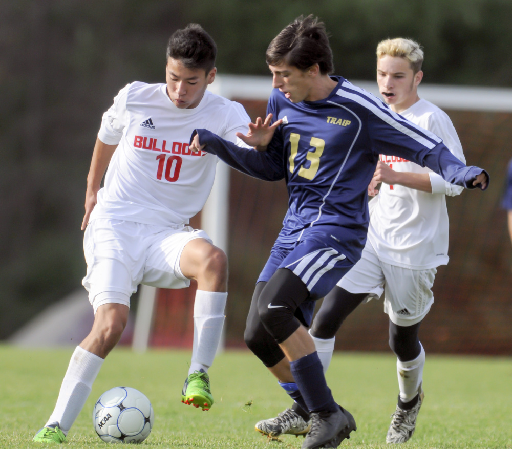 Akira Warren, left, of Hall-Dale tries to shield the ball from Traip Academy's Jacob Gagner during a Class C South boys' soccer semifinal Saturday in Farmingdale. Seventh-seeded Traip advanced with a 2-0 victory.