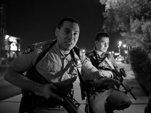 POLICE OFFICERS advise people to take cover near the scene of a shooting near the Mandalay Bay resort and casino on the Las Vegas Strip on Sunday in Las Vegas.