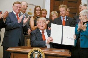 PRESIDENT DONALD TRUMP shows an executive order on health care that he signed in the Roosevelt Room of the White House Thursday in Washington.