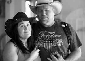 COUNTRY MUSIC FAN JULIE HART and her boyfriend Mark Gay pose for a photo as they recount fleeing from the shooting at the Route 91 Harvest festival Oct. 1 in Las Vegas, at her family home in Anaheim Hills, California. Hart and Gay rushed out onto the airport fence, running with a group of people across the runways towards the terminals on the other side of McCarran International Airport in Las Vegas, as they realized they were being riddled with bullets.