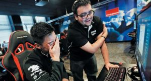 """ROBERT MORRIS UNIVERSITY freshman, Alex Chapman, left, is critiqued by assistant coach Jose Carrasco as he practices playing the video game """"League of Legends"""" with their collegiate teammates at their on-campus training facility in Chicago."""
