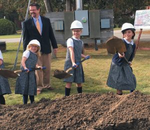 ST. JOHN CATHOLIC SCHOOL third grade students from left, Maddie Smith, Eliza Davis and Aurora Blier get to work Sunday afternoon moving dirt where the new community building will be constructed.