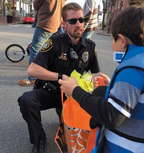 BATH POLICE PATROLMAN Brett McIntire hands out candy to a trick-or-treater during the Soggy Dog Designs' 9th Annual Trick or Treat TROMP in downtown Bath on Saturday, in the photo above. Left, a miniature horse owned by Susan Zimmerman and driven by Kassidy Gustafson of Woolwich Central School takes youngsters for rides at the city park by Patten Free Library. Due to Monday's storm, some towns decided to postpone all Halloween activities until Friday, including Brunswick's annual parade. Topsham officials also urged all families to also postpone their trick or treating until Friday as well, due to a concern that there may be areas still difficult or dangerous to access Tuesday night.