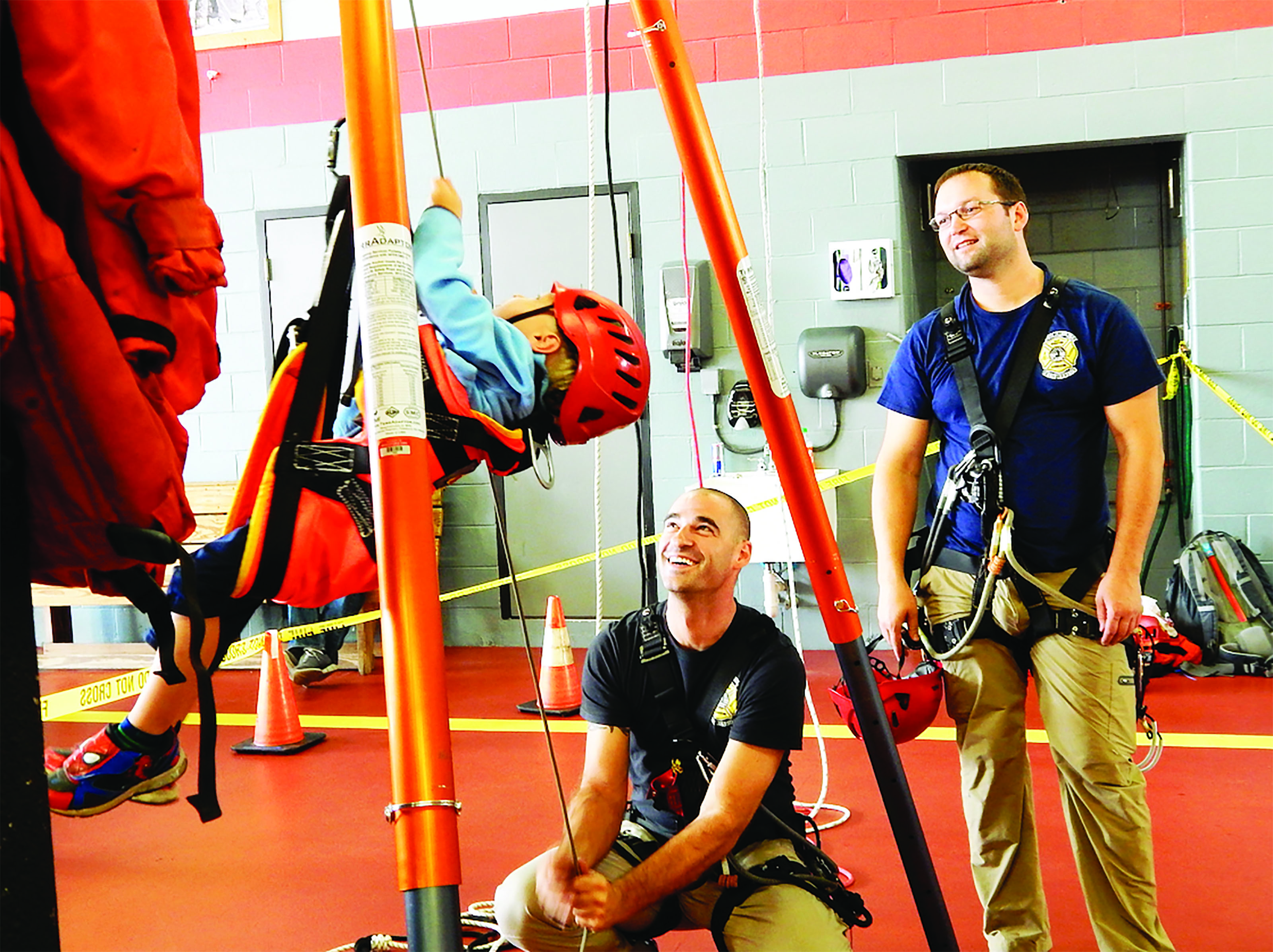 Biddeford firefighters teach a child how to rappel during the fire department's annual open house held at the Biddeford Fire Station on Saturday. ED PIERCE/Journal Tribune