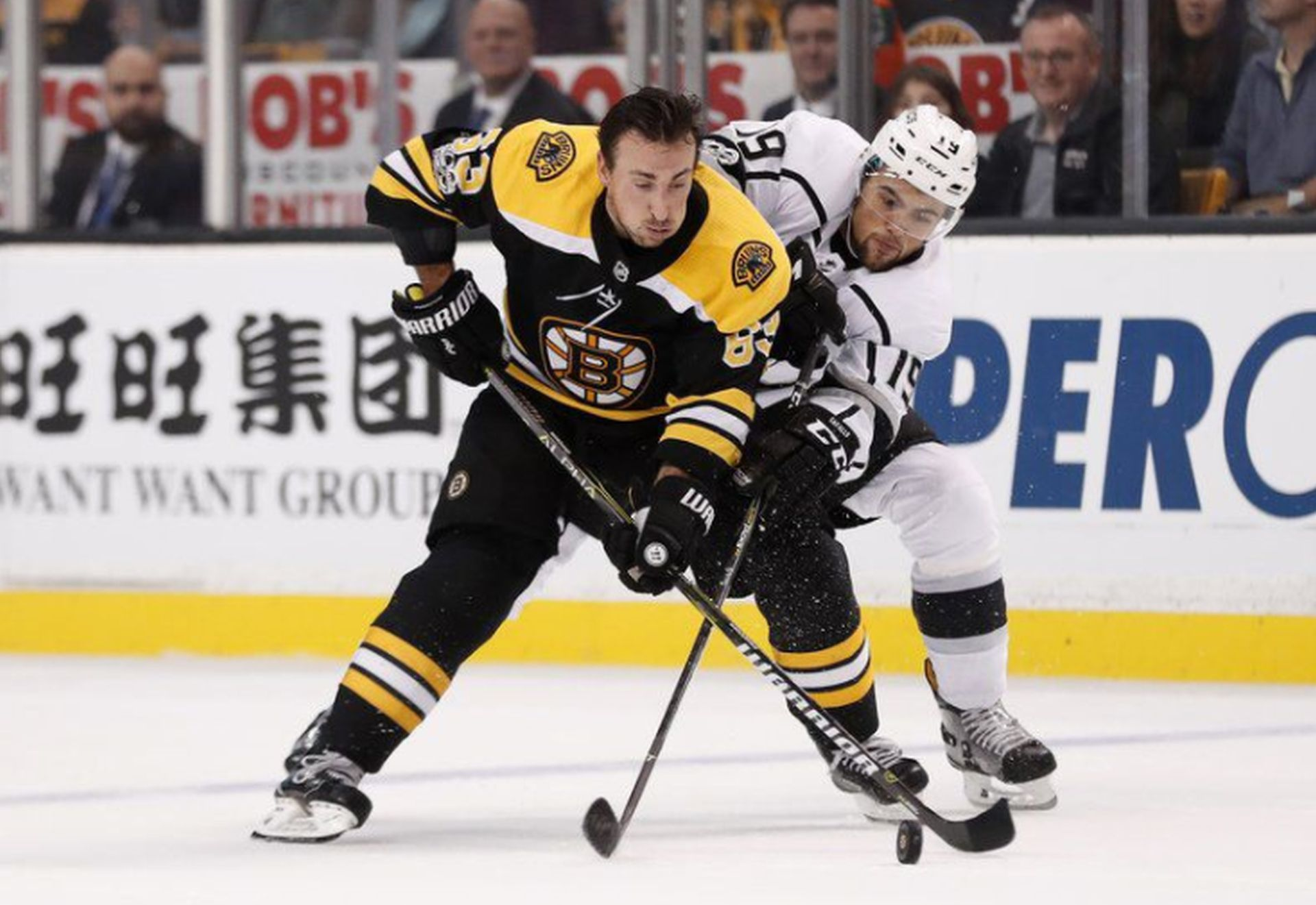 Brad Marchand of the Boston Bruins tries to keep Los Angeles Kings' Alex Iafallo (19) from the puck during a National Hockey League game in Boston on Saturday night. AP NEWSWIRE/Winslow Townson