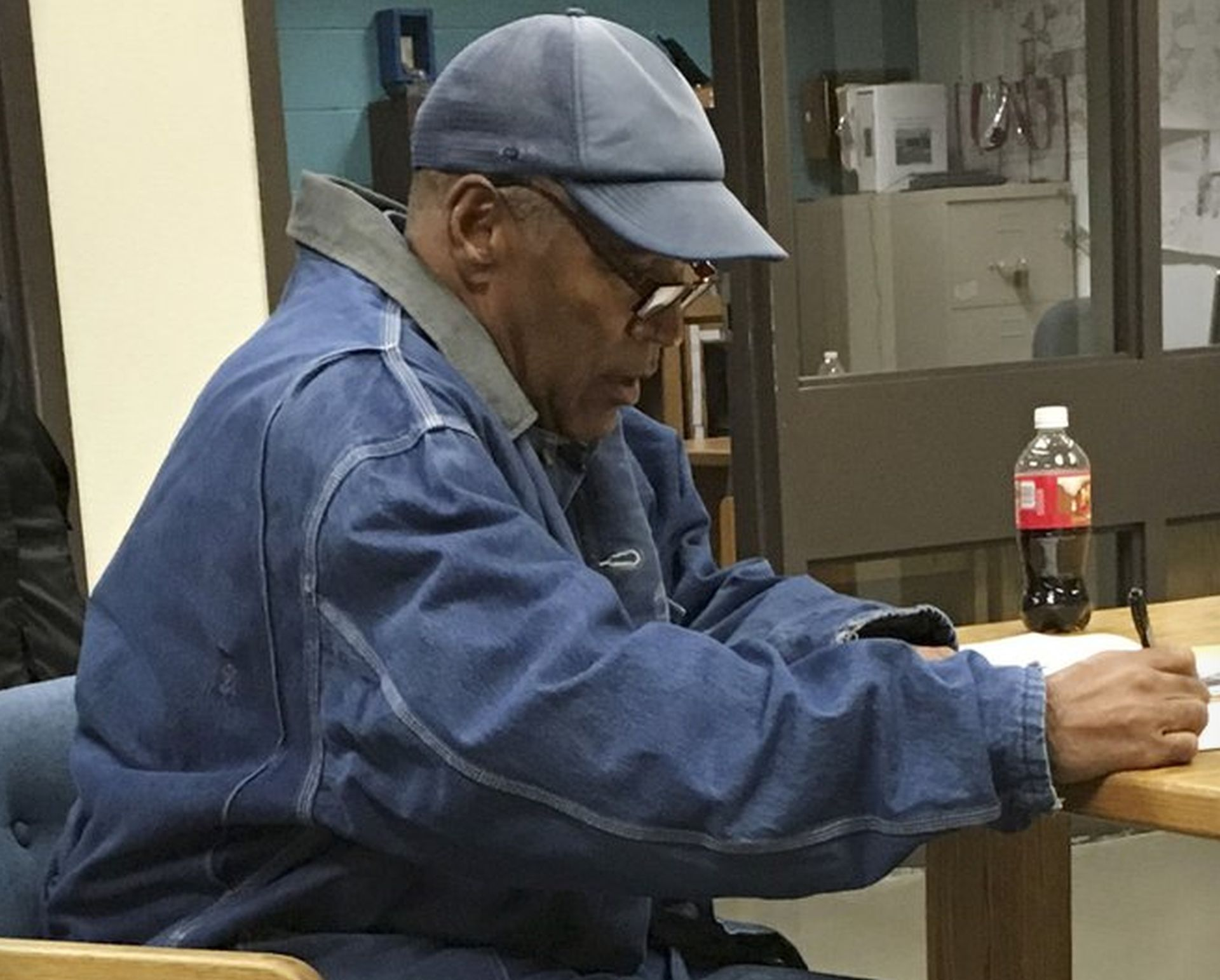 OJ Simpson signs documents regarding his release from the Lovelock Correctional Center in Nevada just before his release Sunday, Oct. 1, 2017. AP NEWSWIRE/Brooke Keast, via AP