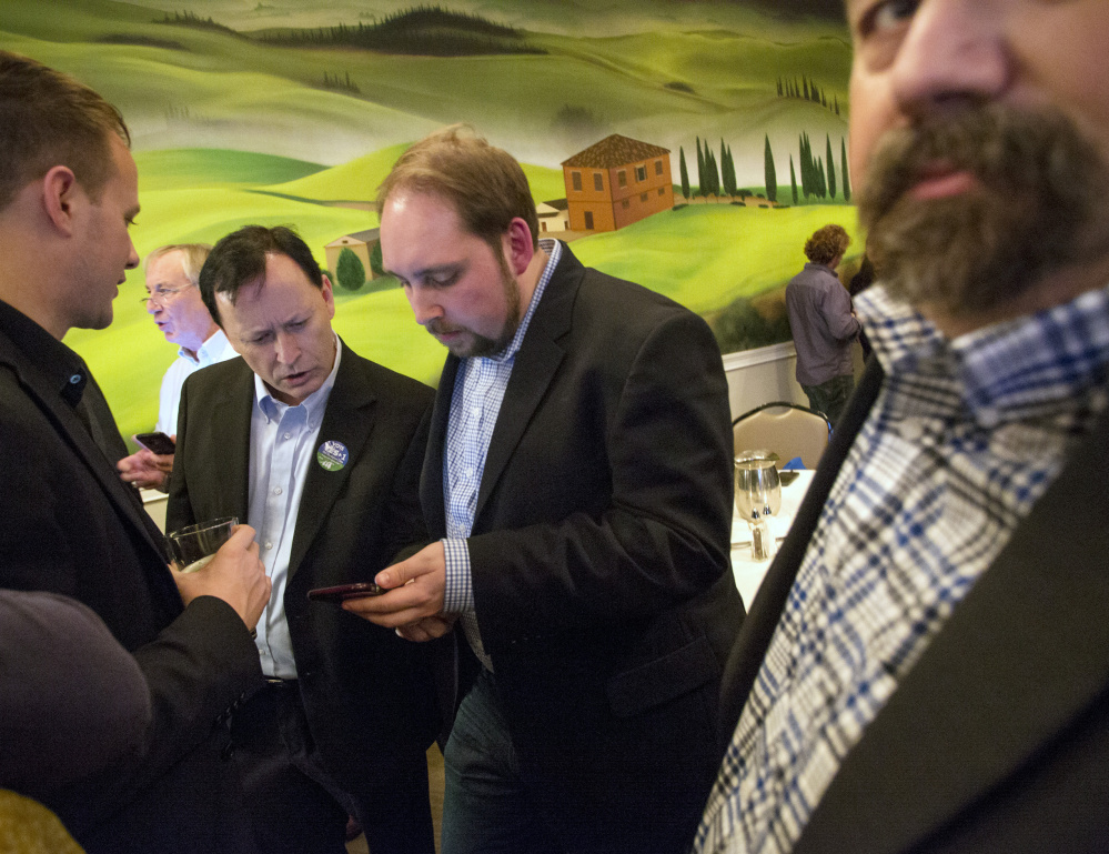 Entrepreneur Shawn Scott, center left, looks at the phone of Yes on 1 campaign press secretary Michael Sherry during a gathering of York County casino supporters Tuesday evening at Bruno's Restaurant in Portland.