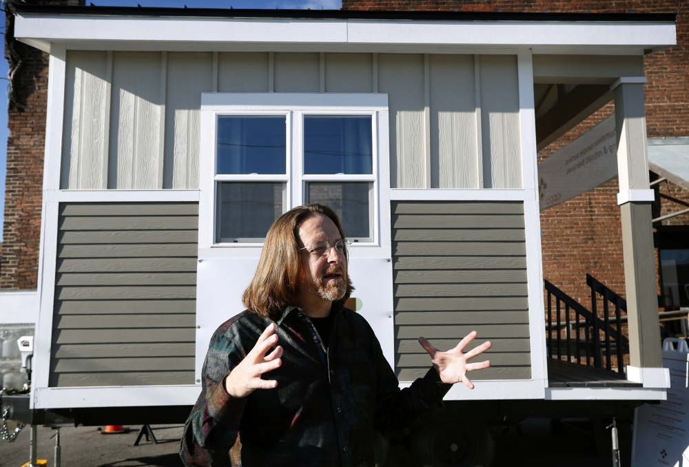 "Joe Stevens stands in front of one of the tiny homes his student group built in hopes of helping the homeless in Des Moines, Iowa. ""We're not giving up,"" he said."