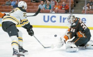 ANAHEIM DUCKS goalie John Gibson, right, blocks a shot by Boston Bruins left wing Peter Cehlarik during the first period of an NHL hockey game in Anaheim, Calif. on Wednesday.
