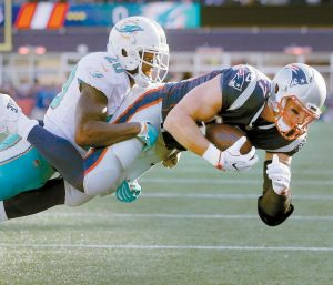 NEW ENGLAND PATRIOTS tight end Rob Gronkowski, right, scores a touchdown with Miami Dolphins safety Reshad Jones on his back during the first half of an NFL football game on Sunday in Foxborough, Mass. The Patriots won, 35-17.
