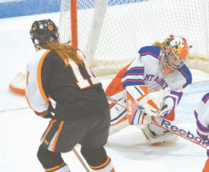 EAGLES' LILY SCHENK (right) makes one of her 28 saves on an Ashley Atwater shot (left) in Friday night's loss to the Tigers.