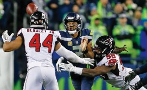 SEATTLE SEAHAWKS quarterback Russell Wilson, center, gets off a pass as he is hit by Atlanta Falcons' Adrian Clayborn (99) as Vic Beasley moves in in the second half of an NFL football game on Monday in Seattle. The Falcons won, 34-31.