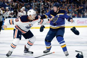 EDMONTON'S MATT BENNING, left, and St. Louis Blues forward Vladimir Tarasenko fight during the second period of an NHL hockey game on Tuesday in St. Louis. The Blues won, 8-3.