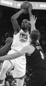 GOLDEN STATE Warriors' Kevin Durant (35) shoots between Miami Heat forward Justise Winslow (20) and Kelly Olynyk, right, during the second half of an NBA basketball game Monday in Oakland, Calif. Warriors won, 97-80.