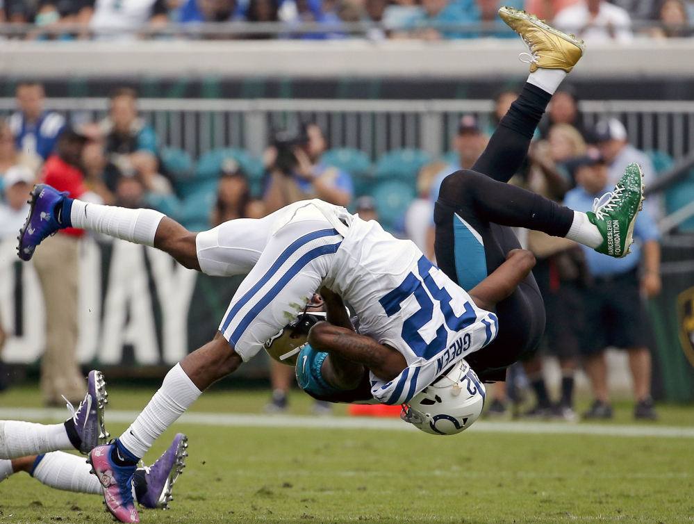 Jaguars tight end Marcedes Lewis, back, is tackled Sunday by Colts safety T.J. Green during Jacksonville's 30-10 win that kept the Jaguars tied with Tennessee atop the AFC South.