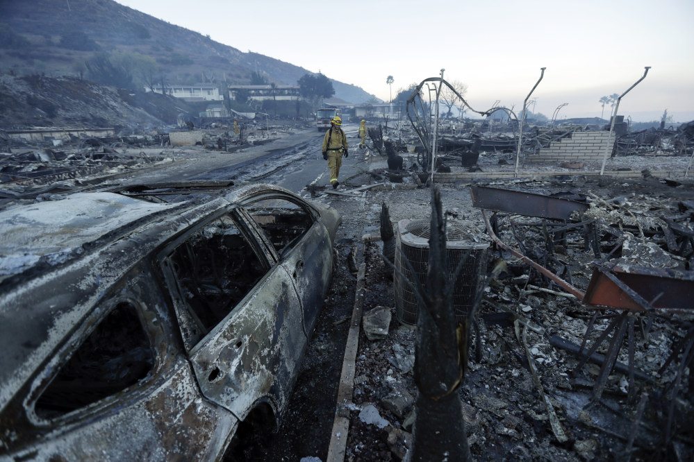 Fire crews search for hot spots among destroyed homes in the Rancho Monserate Country Club community Friday in Fallbrook, Calif. The wind-swept blazes have forced tens of thousands of evacuations and destroyed more than 1,000 buildings in Southern California.