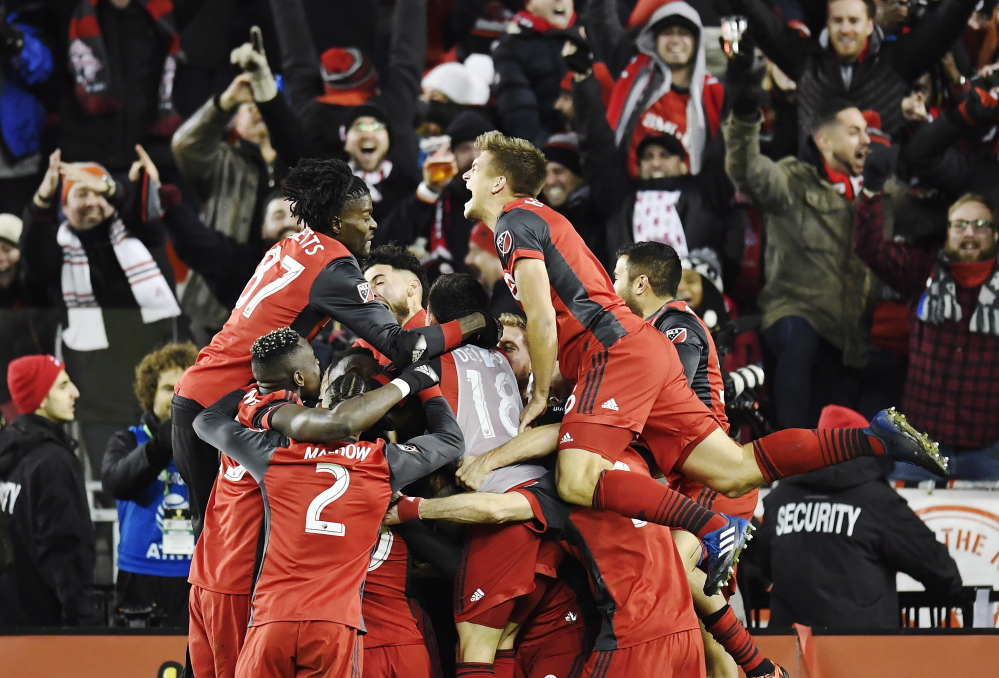 Toronto FC players celebrate their second goal against the Seattle Sounders in the final minutes of the MLS Cup final in Toronto on Saturday. Toronto FC won the title, 2-0.