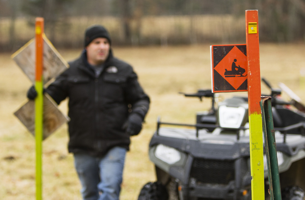 Jeb Pruett, a member of the Windham Drifters Snowmobile Club, helps mark trails early Saturday in preparation for the season. The club looks after about 45 miles of trails. All told, snowmobilers contribute $350 million annually to the state's economy.