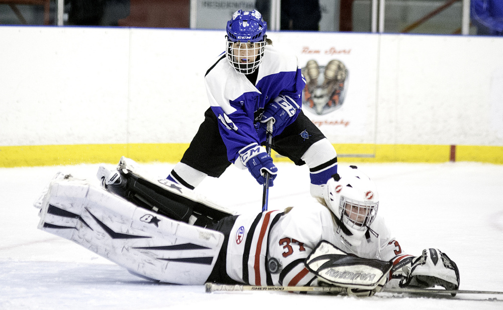 Scarborough goalie Grace Carriero makes a diving save on a shot in front of Lewiston's Sara Roberts during a girls' hockey game Saturday in Lewiston. The Blue Devils remained undefeated with a 6-1 win.
