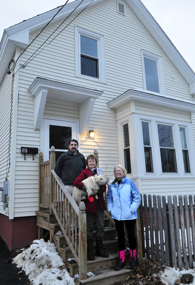 Waterville Community Land Trust members Scott McAdoo, Francis Williams and Ann Beverage at a home the organization bought and is selling at 181 Water St. in Waterville on Monday.