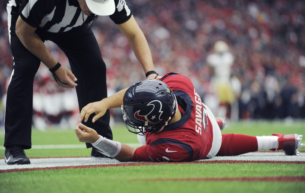 Texans quarterback Tom Savage is checked by a referee after he was hit Sunday during a game against the San Francisco 49ers. The NFL will review whether the Texans followed the concussion protocol properly.