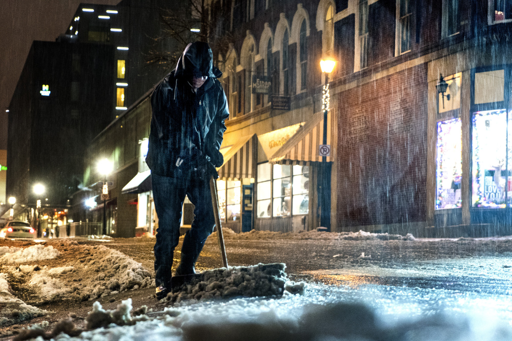 As heavy rain falls around him, Mike Brown of Maxwell Pottery clears snowy slush in front of his Fore Street business during the evening commute Tuesday. Conditions from the all-day storm led to several accidents and slide-offs, but no serious injuries.