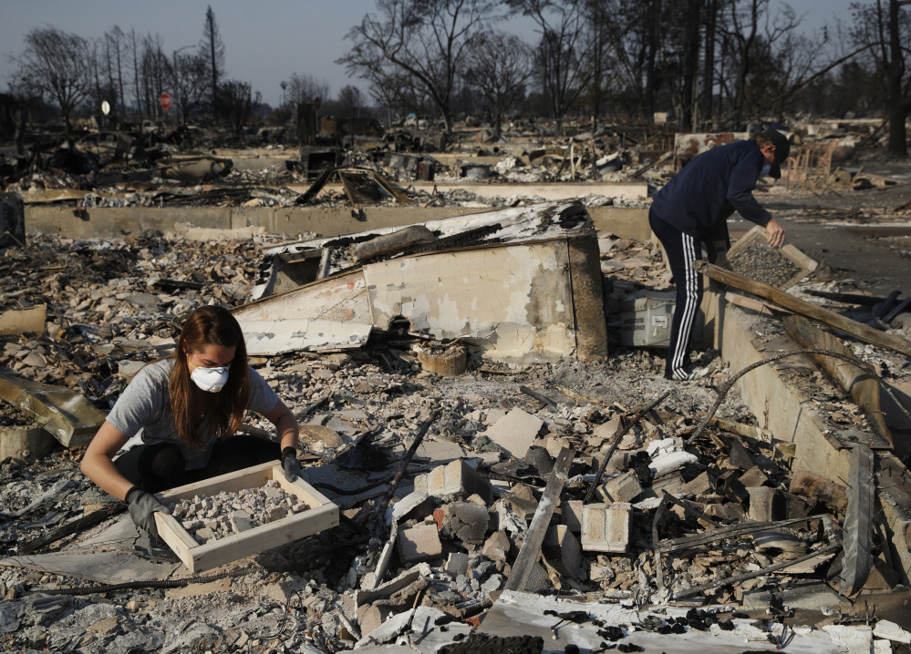 A family works to salvage materials from the rubble of their home, which was destroyed by a wildfire in Santa Rosa, Calif. in October. If House Republicans have their way, victims of hurricanes in Texas and Florida could deduct their losses on their taxes, but California wildfire victims no longer could do so.
