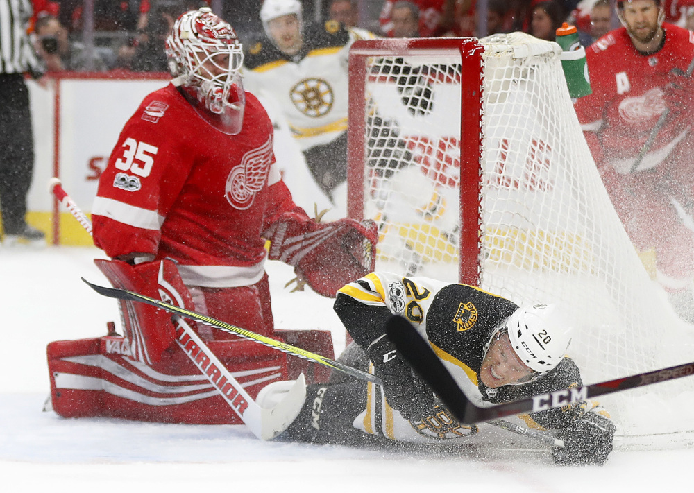 Bruins center Riley Nash slides into the net and Red Wings goalie Jimmy Howard in the first period.