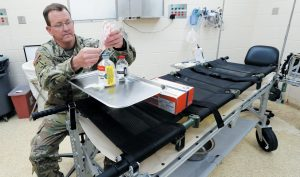U.S. ARMY COL. SHAWN KANE demonstrates the use of freeze-dried plasma in the military at Fort Bragg, North Carolina. All of the U.S. military's special operations fighters sent off to war zones and raids now have the essential addition to their first-aid kits. The plasma helps clot blood and can prevent badly wounded troops from bleeding to death on the battlefield.