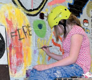 STUDENTS AND ARTVAN STAFF work on a mural at the Bath Youth Meetinghouse and Skate Park, in the photo at the top. Above, 7th grade student Natalie Kettell works on the mural at the Bath Youth Meetinghouse and Skate Park.