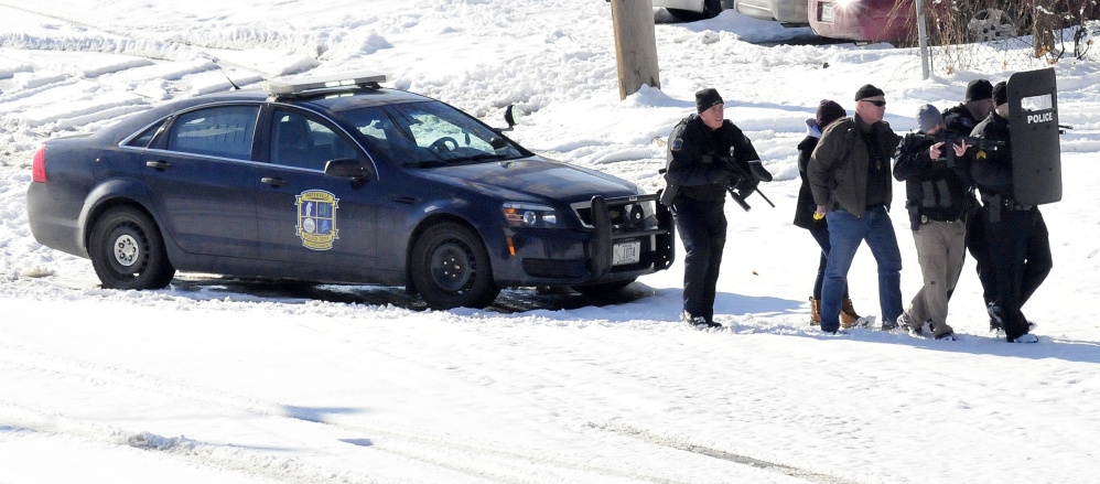 Waterville police and negotiators slowly approach Michael Joslyn at 124 College Ave. in Waterville on Sunday where they shot pepper-balls to subdue Joslyn after a 13-hour standoff at the apartment.