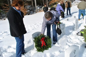 Wreaths were laid on the graves of veterans on Wreath Across America day at the Southern Maine Veterans' Cemetery in Springvale on Saturday. Elaine Baron and Janet Jepson place a wreath on the grave of their father, Roland Carrier who served in the U.S. Navy. DINA MENDROS/Journal Tribune
