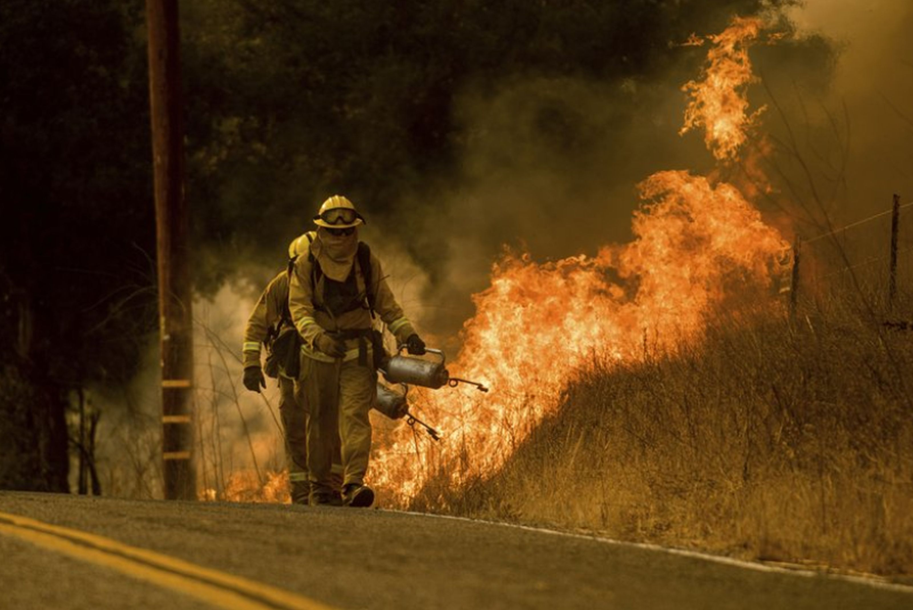 Firefighters light backfire while trying to keep a wildfire from jumping Santa Ana Road near Ventura, Calif. AP NEWSWIRE/Noah Berger