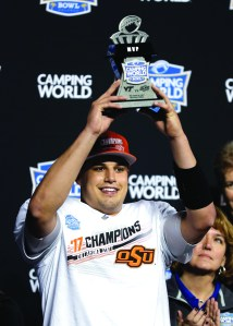 Oklahoma State quarterback Mason Rudolph holds up the MVP trophy after Oklahoma State defeated Virginia Tech 30-21 in the Camping World Bowl game Thursday. AP NEWSWIRE