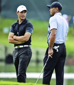 In this May 6, 2015, file photo, Tiger Woods, right, talks with swing coach Chris Como on the 17th green during a practice round for The Players Championship golf tournament at Sawgrass in Ponte Vedra Beach, Fla. Woods is embarking on his latest comeback without a swing coach, saying he has worked hard to relearn his body and the golf swing. Como has helped him the last three years. AP NEWSWIRE